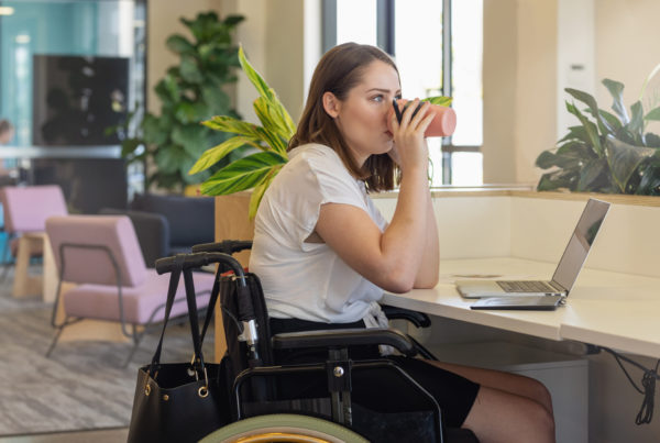 Young woman in a wheelchair sipping a drink at her desk