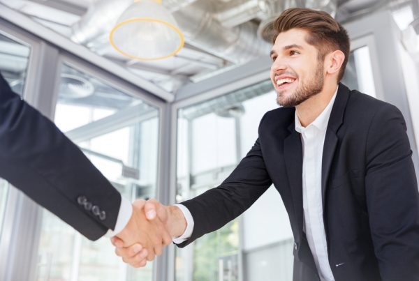 Two young men in suits shaking hands