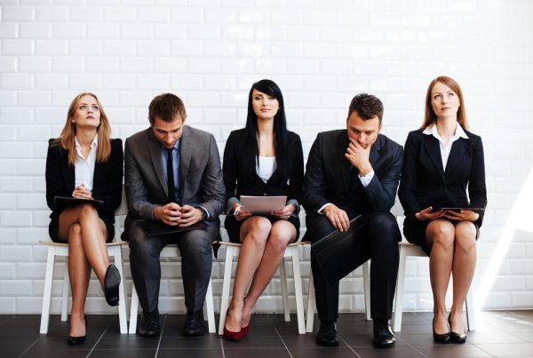 A group of young business professionals dressed in suits waiting for a job interview