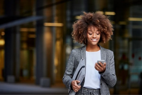 Business woman in a white shirt and grey blazer holding a phone