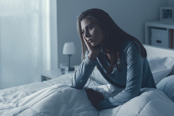 woman sat on a bed looking depressed