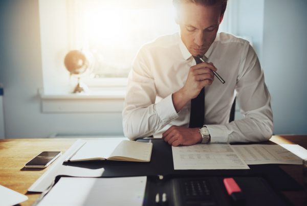 Man in tie sat at desk with documents
