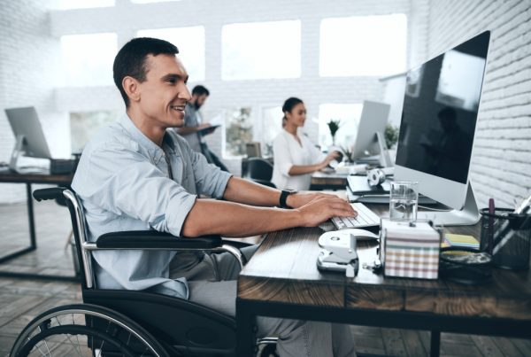 A guy in a wheelchair at a desk with a computer