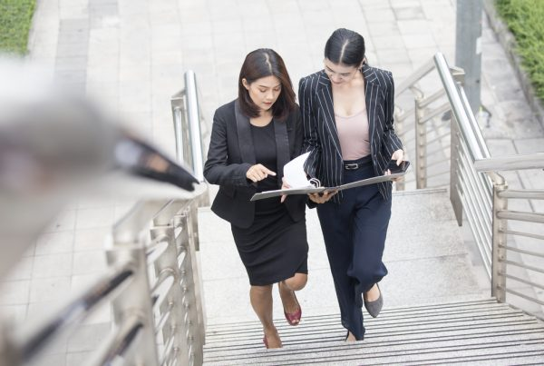 Two female lawyers in suits walking up a flight of stairs