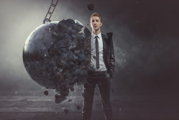 A young man in a suit with a wrecking ball