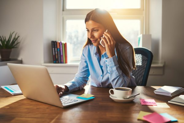 Business woman with laptop using mobile phone