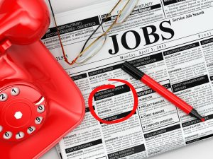 Newspaper listing job adverts and a red telephone