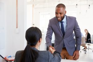 Man in a suit shaking hands with a female
