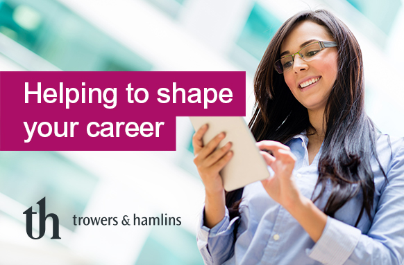 Trowers logo with a young woman in a smart outlfit looking at a tablet