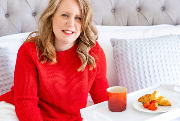 Laura Brunnen in a red jumper with a red mug, strawberries & croissant