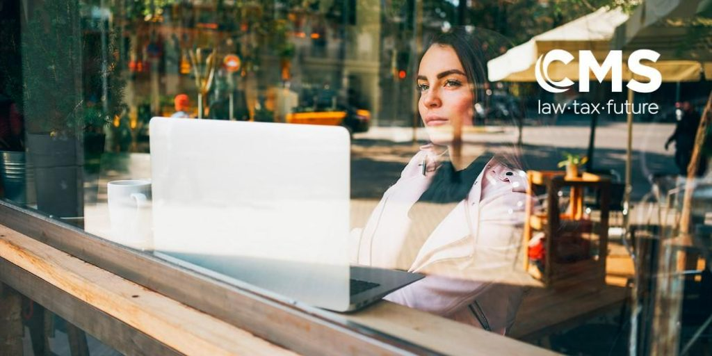 CMS branded image of a young woman sat in front of a laptop